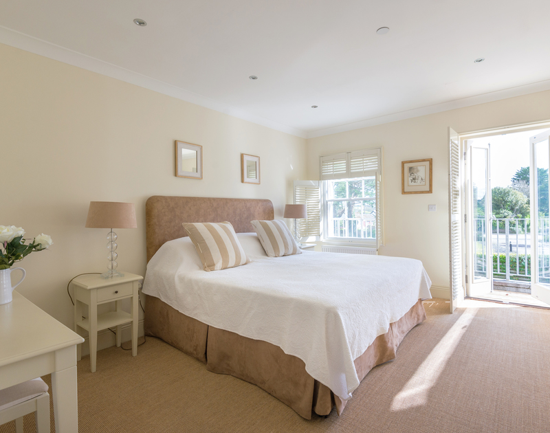 A spacious double bedroom with balcony at Lowenna Manor 5, a holiday house in Rock, Cornwall, with zip and link beds.