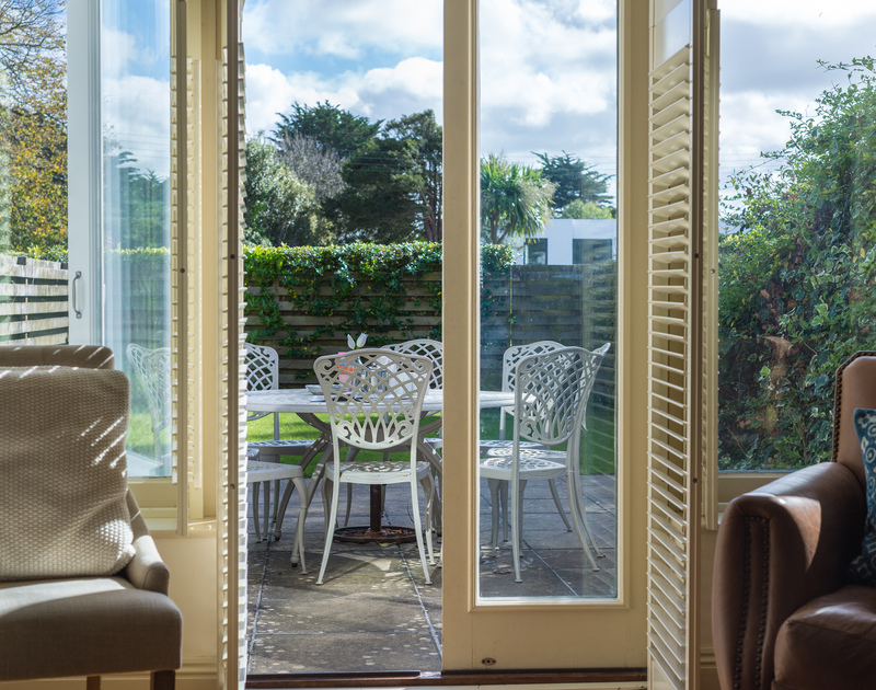 The view through the french doors to the patio in the enclosed garden from the sitting room at Lowenna Manor 5 in Rock, North Cornwall.