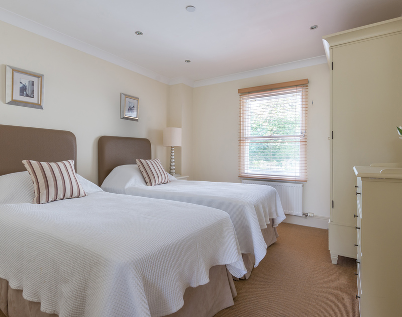 A bedroom with zip and link twin beds at Lowenna Manor 5, a holiday house to rent in Rock, Cornwall