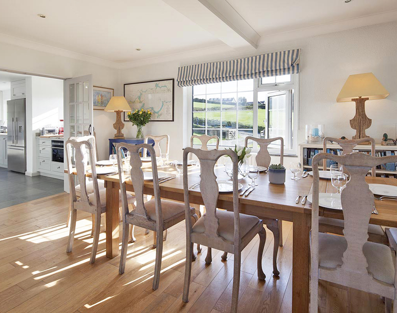 The spacious open plan dining / living room at Spindrift, a holiday house to rent at Daymer Bay, with its long table seating 12 people.
