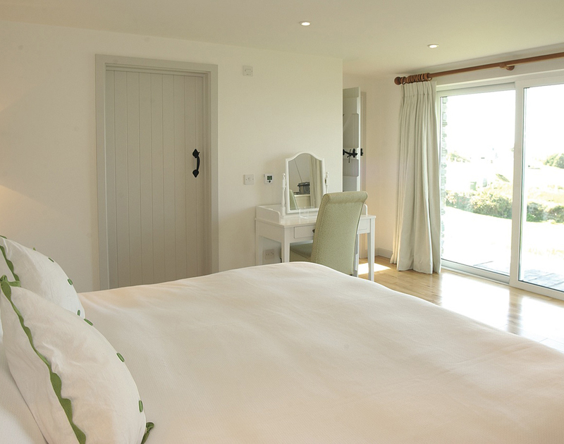 The master bedroom of Sprindrift, a holiday house near Daymer Bay, with patio doors to the garden and a private terrace.