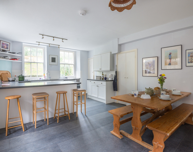 A practical breakfast bar and dining table in the kitchen at 4, The Terrace, a fabulously located Cornish holiday property on the Camel Estuary.