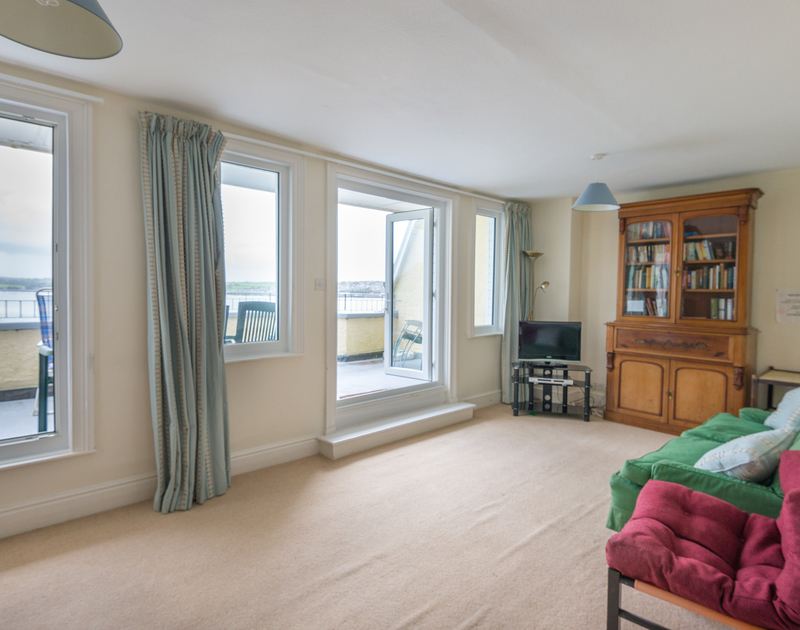 The large snug at 4, The Terrace with glass doors onto the balcony overlooking Padstow and the Camel Estuary.