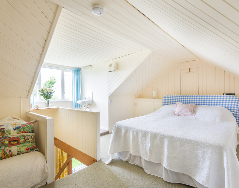 The master bedroom accessed via a steep staircase in a pretty converted attic setting in Avoca, a holiday rental in Rock, Cornwall.