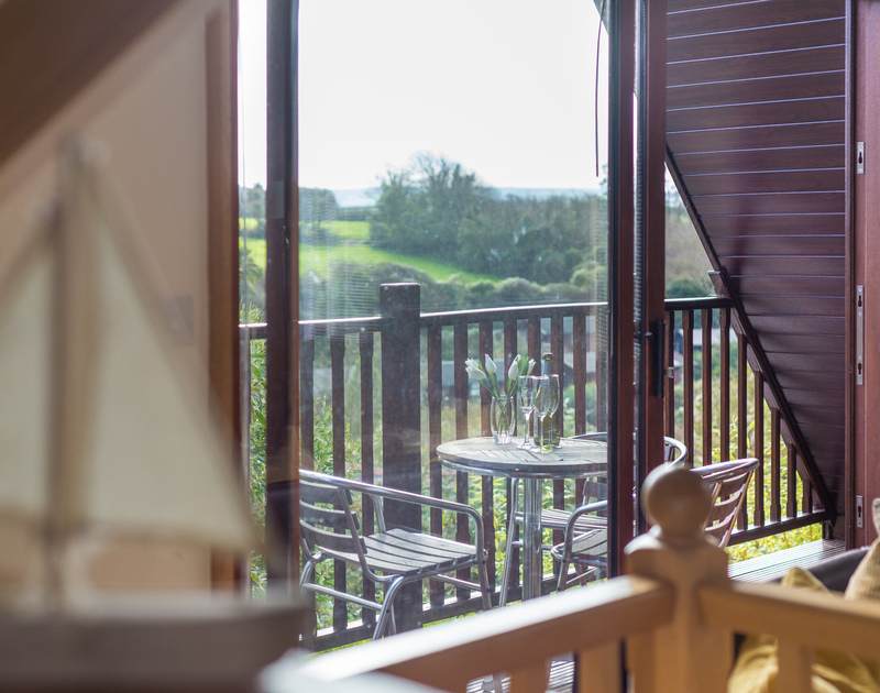 Relax with a drink and enjoy the rural views from the balcony at 8, Sandy Hills, a self catering holiday house in Rock.