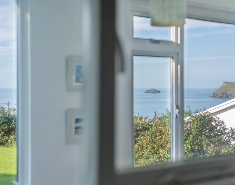 The window of the double bedroom at Trewint frames the island and Pentire Point at Polzeath in Cornwall.