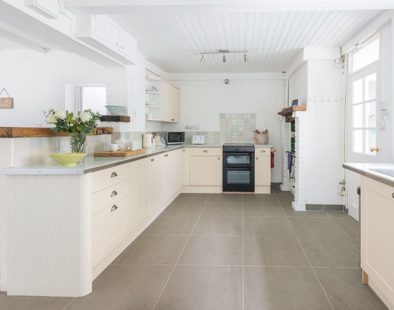 The stylish and modern kitchen has an external door leading out to the sheltered garden terrace at Signal Post, a self catering holiday house in Port Isaac.