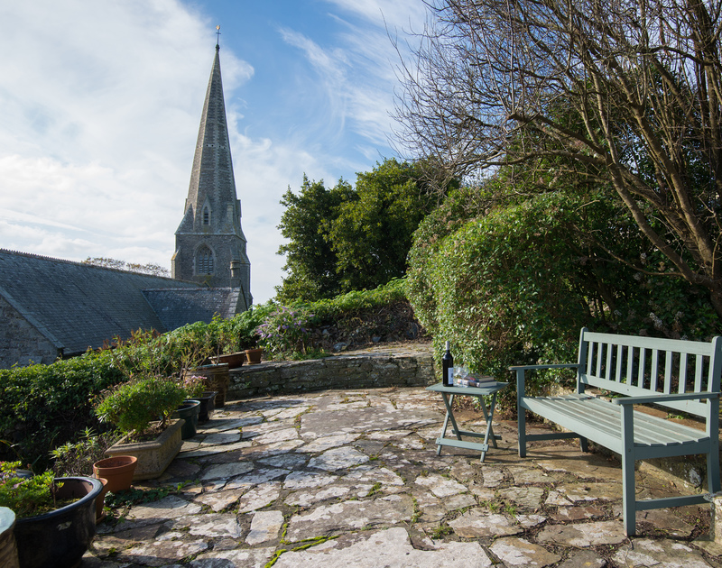 Relax on the sheltered terrace at self catering, Honeysuckle Cottage alongside the comically, wonky spire of St Menefreda Church.