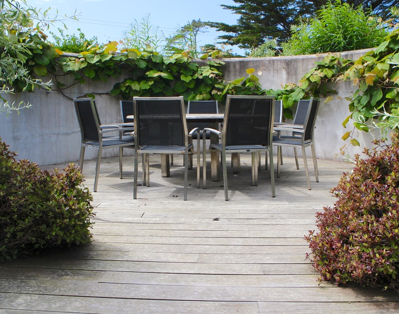 Sheltered, wooden decked patio area for alfresco meals or drinks at Church Lane House, a luxurious self catering holiday house in Daymer Bay.