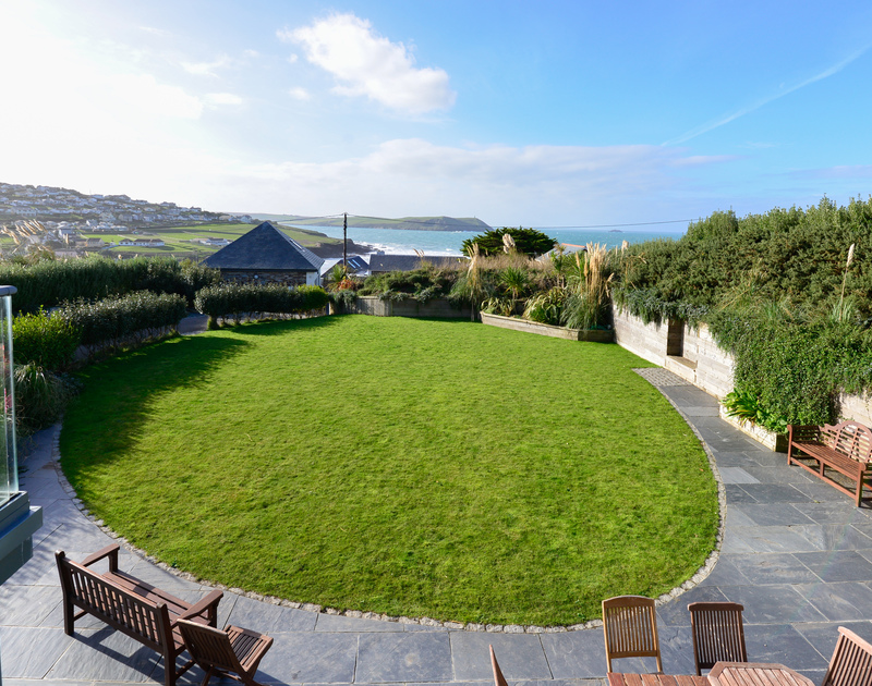 The circular lawn with blue slate patio and garden furniture at Clouds Hill, a luxury, self catering, holiday house in New Polzeath, North Cornwall.