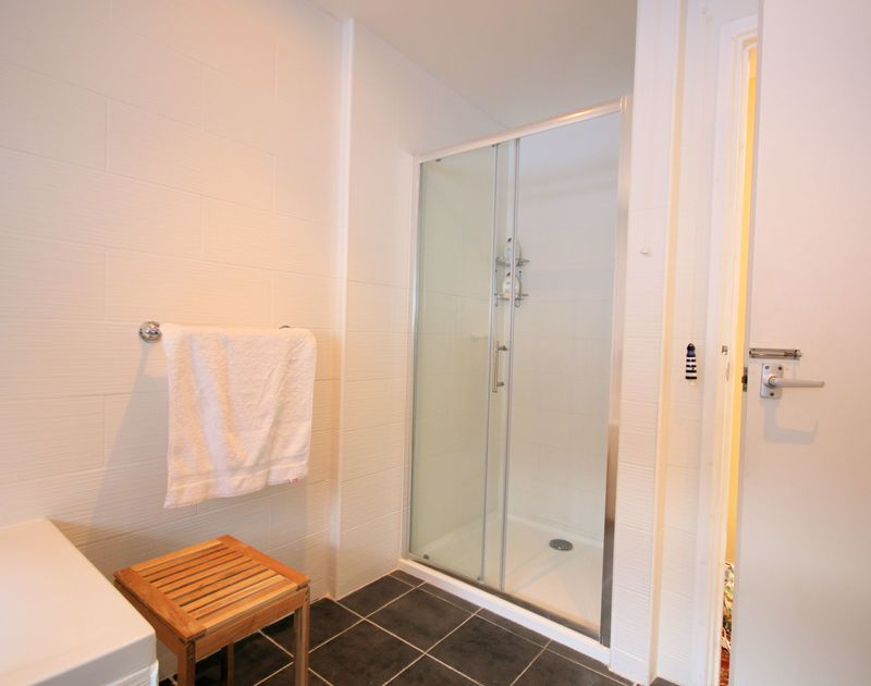 The family bathroom with an enclosed shower unit at Stradav a self catering holiday house by the sea in Polzeath, Cornwall.