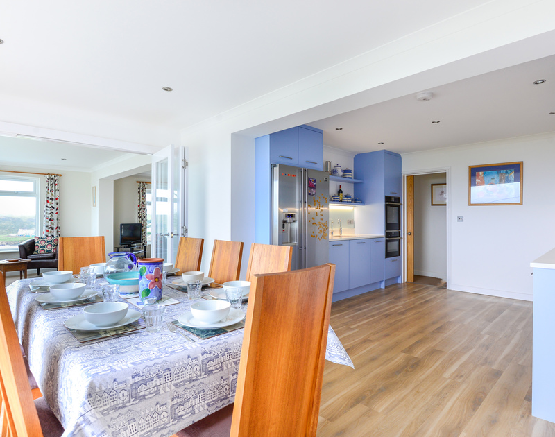 The cool blue kitchen and dining table in Sea Mist an open plan, self catering holiday house to rent in Polzeath.