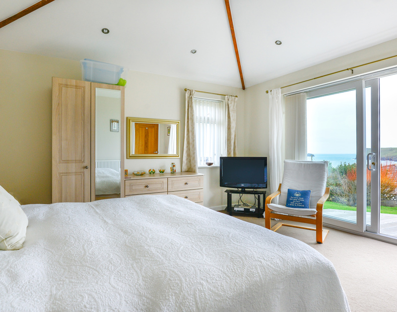 The master bedroom at Sea Mist has patio doors leading out to the terrace and gardens with stunning coastal views over the sea at Polzeath .