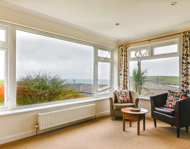 Relax in one of the windows of the sitting room at Sea Mist, a self catering, holiday property to rent overlooking the sea at Polzeath in Cornwall.