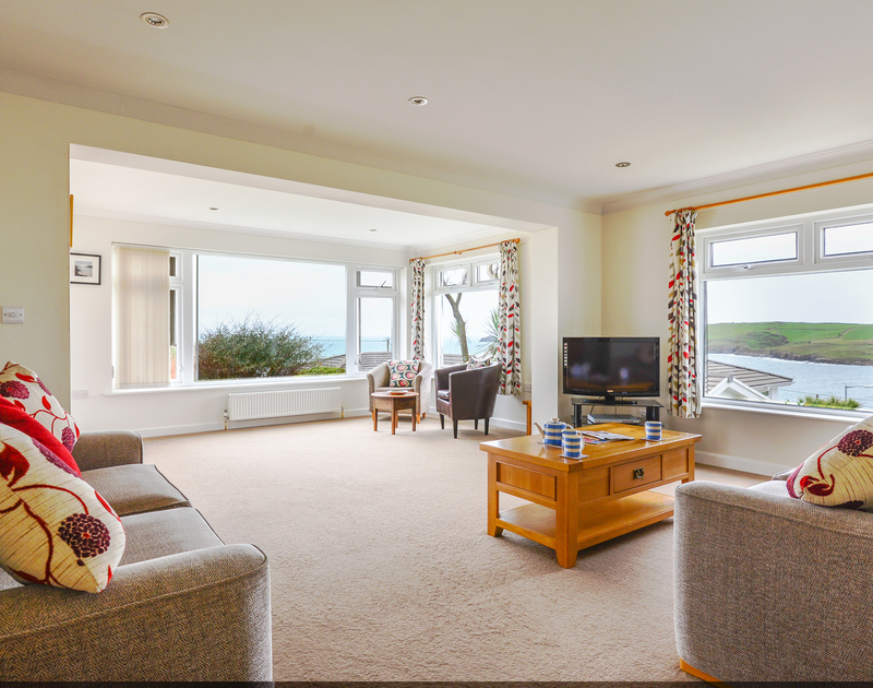 All the many windows in the sitting room at Sea Mist a self catering holiday rental, have views of the sea at Polzeath and Pentire Point.