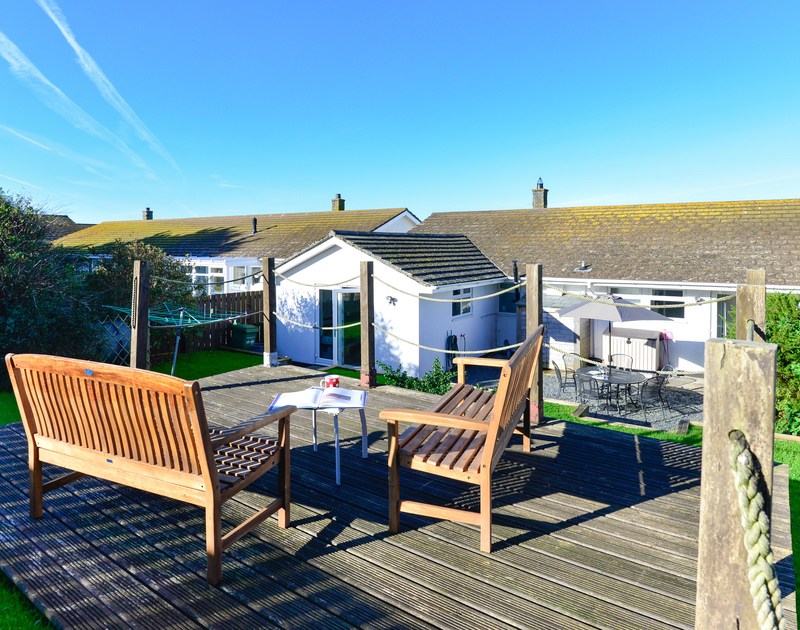 Bask in the sunshine or enjoy a cuppa on one of the garden benches on the raised decked terrace at Silvershell House, a self catering holiday bungalow in Port Isaac in North Cornwall.