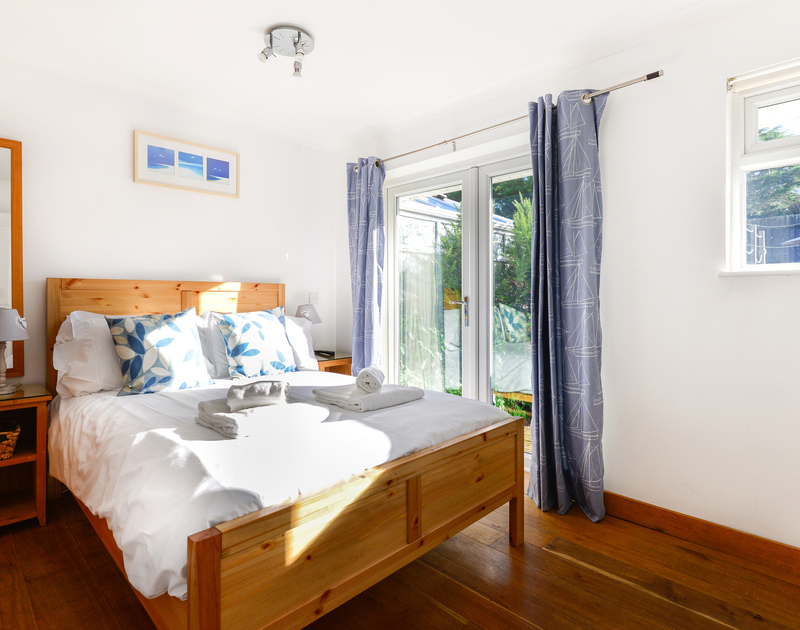 Glass patio doors fill the double bedroom with Cornish sunlight at self catering holiday rental Silvershell House in Port Isaac in North Cornwall.