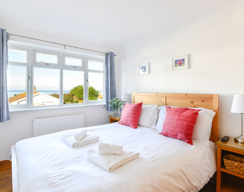 The master bedroom with sea views through the large windows at Silvershell House, a self catering holiday property in Port Isaac in Cornwall.