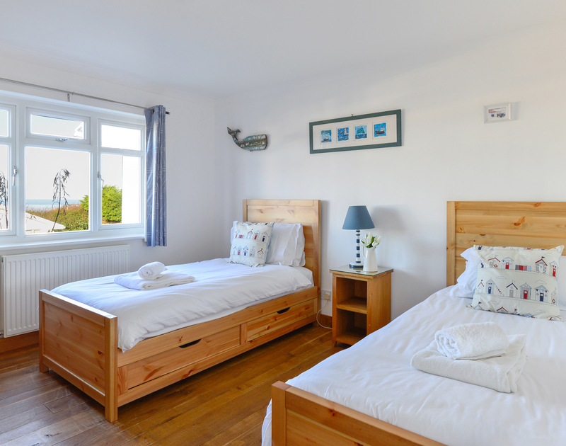 The twin bedroom with sea views and a coastal theme at self catering holiday rental Silvershell House,a  well appointed holiday bungalow in Port Isaac in North Cornwall.