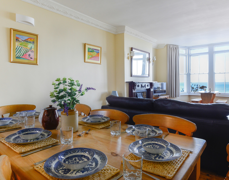 Holiday meals around the table in the open plan sitting/dining room with memorable, panoramic sea views through the bay window at Seaview, a self catering holiday house in a stunning setting overlooking Port Gaverne beach in Port Issac.