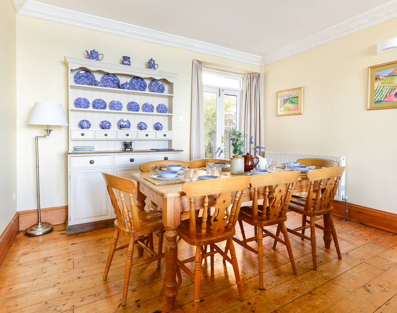 The high ceilings, decorative coving and warm wooden floorboards in the spacious sitting/dining room at Seaward, a well appointed Edwardian terraced holiday house with fabulous views in Port Isaac on the North Cornish Coast.