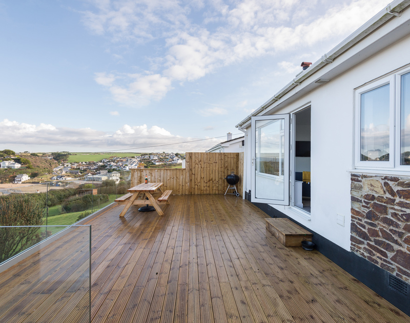 Large wooden decked terrace with a glass balustrade at seaside holiday house Trelorna located just above Polzeath beach at Tristram in Cornwall.
