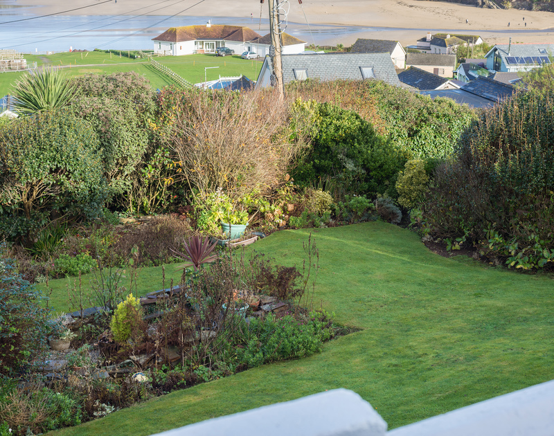 The seaside garden at Trelorna with a lawn and mature shrubs and plants designed to protect the garden from winter winds or salty summer breezes.