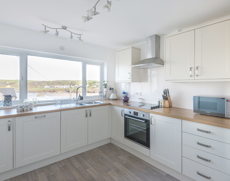 Check the surf whilst washing up or preparing meals in the neat, modern kitchen at seaside holiday house Trelorna in Polzeath.