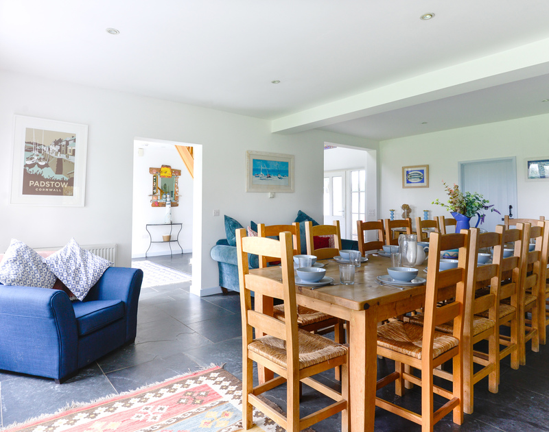 The sociable open plan dining room and kitchen with sofas and lots of light from the double doors to the garden at Trewidden, a self catering holiday house in Daymer Bay, North Cornwall.