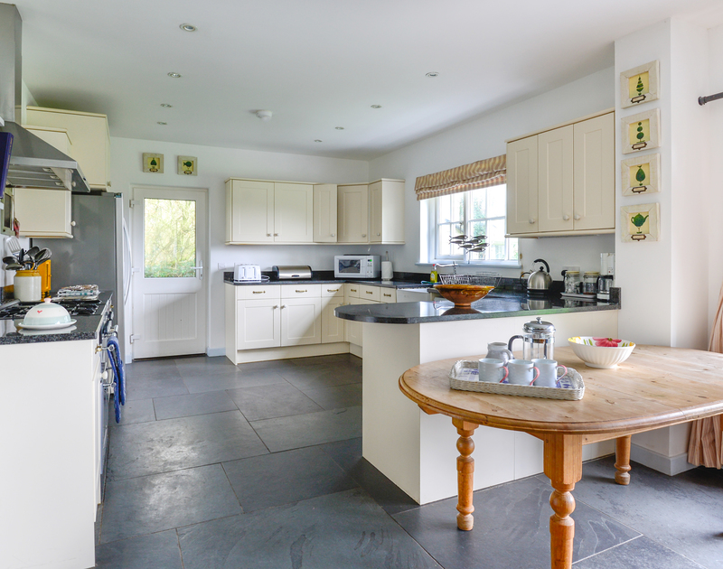 The modern, practical fitted kitchen at Trewidden, a large family, self catering holiday house in Trebetherick, above Daymer Bay in North Cornwall.