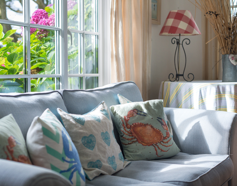 Snuggle up with a book on one of the cosy sofas at self catering, family, holiday house Trewidden in Trebetherick, Cornwall.