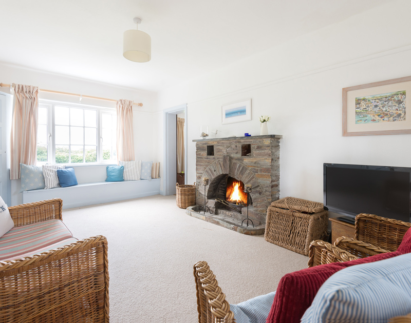 The comfortable sitting room with fireplace in Trewidden, a self catering large family holiday house to rent in Daymer bay, Cornwall.
