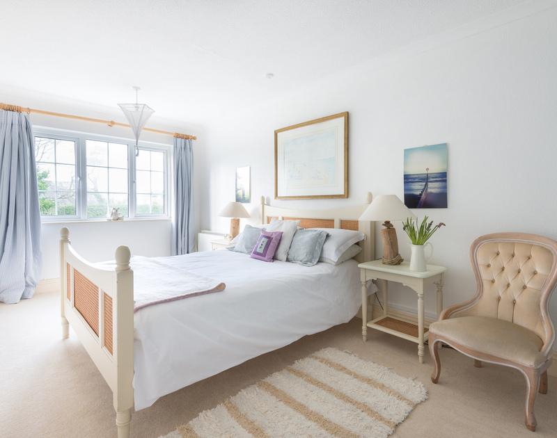 The well-furnished master bedroom of Trewella, a holiday house at Daymer Bay, Cornwall, with king size bed.