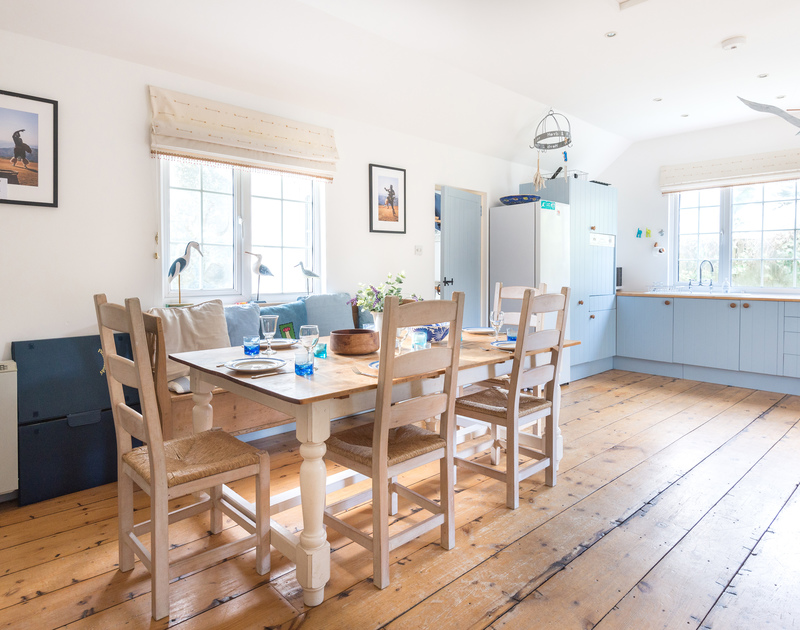 Warm, wooden floorboards in the kitchen/dining room at self catering holiday house Trewella in Daymer Bay in Cornwall.