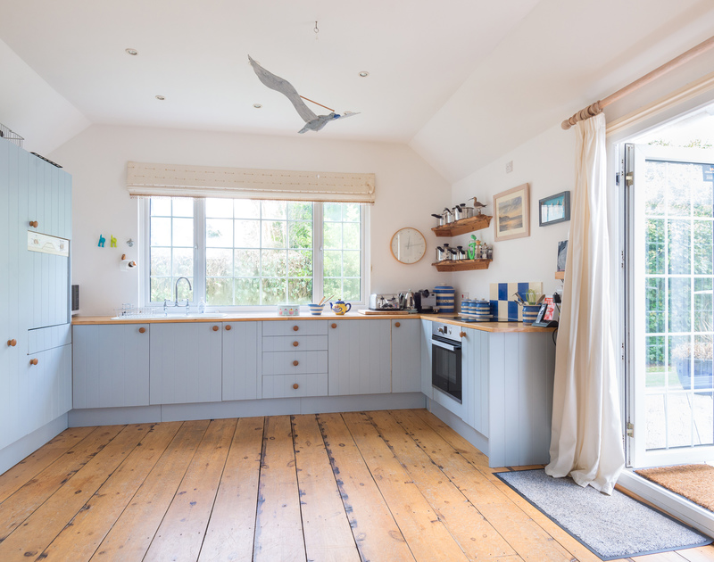 The kitchen area inspired by the coast with pale tones at Trewella, a self-catering seaside holiday house at Daymer Bay, Cornwall