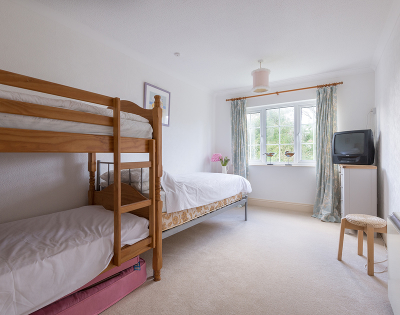 A bright a spacious bunk bedroom with a single bed at Trewella in Daymer Bay