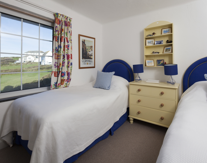 The 4th bedroom at Spindrift, a large clifftop holiday house, is a bold and bright twin room with sea views to the East