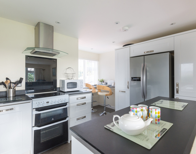 The black and white stylish kitchen of Bedrawle, a holiday rental in Rock, Cornwall, with its breakfast bar.