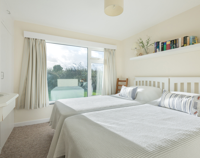 A twin bedroom with garden views through the large picture window at Bedrawle, a holiday rental in Rock, Cornwall