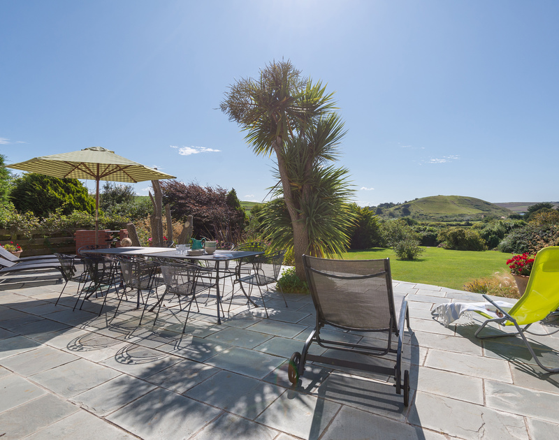 The large, furnished patio of Hob House, a holiday house at Daymer Bay, Cornwall, with views of the Camel Estuary.