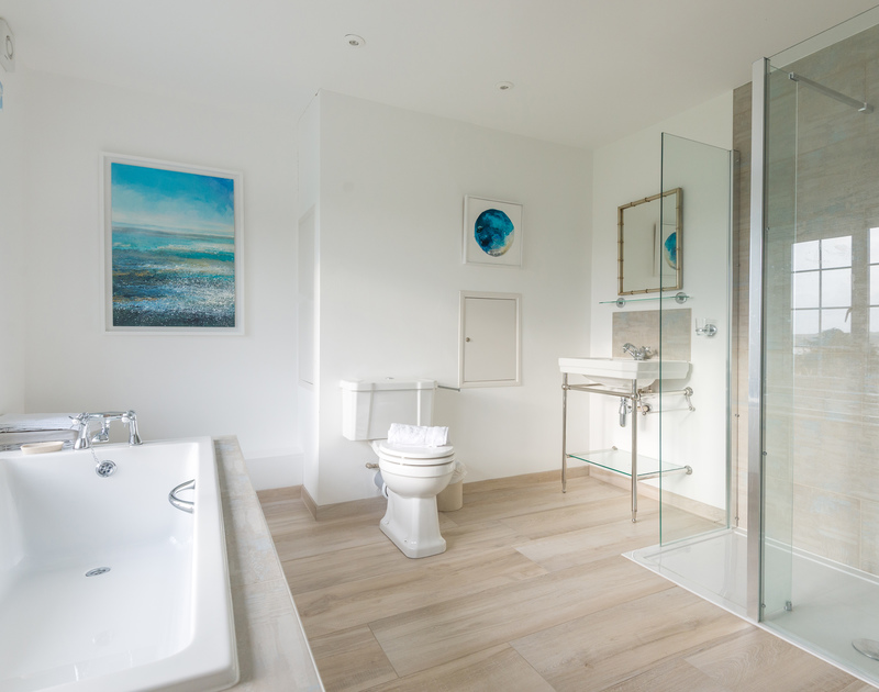 The large contemporary superking bedroom ensuite bathroom with a bath, separate shower, toilet and basin at Hob House.