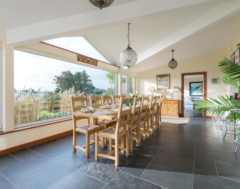 The elegant dining table on the slate floored dining room at Hob House, ideal for a large family celebration or simply memorable holiday mealtimes in Daymer bay.