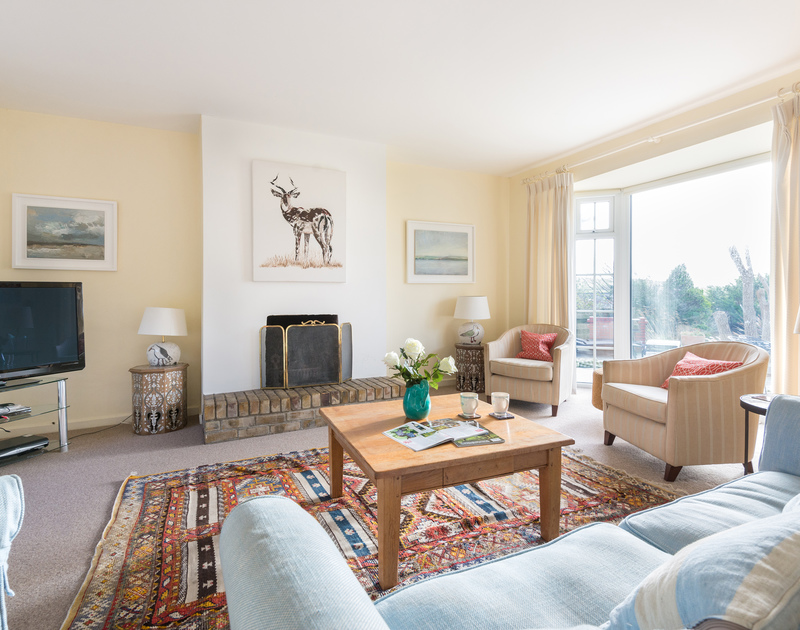 Relax by the fire in the sitting room with access out onto the patio at Hob House