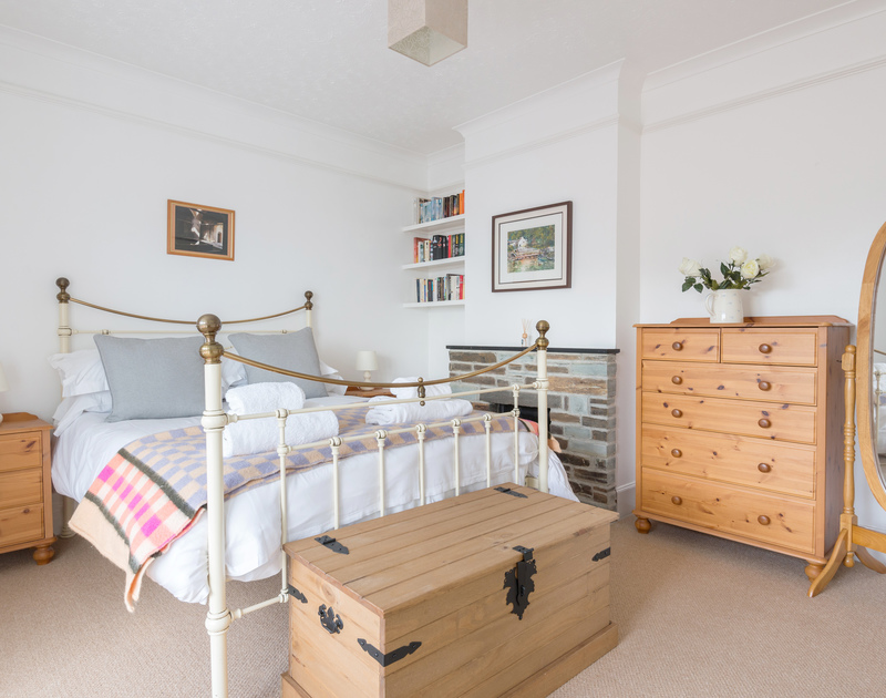 The ground floor double bedroom at Tregenna with a pretty bedstead and sea views.