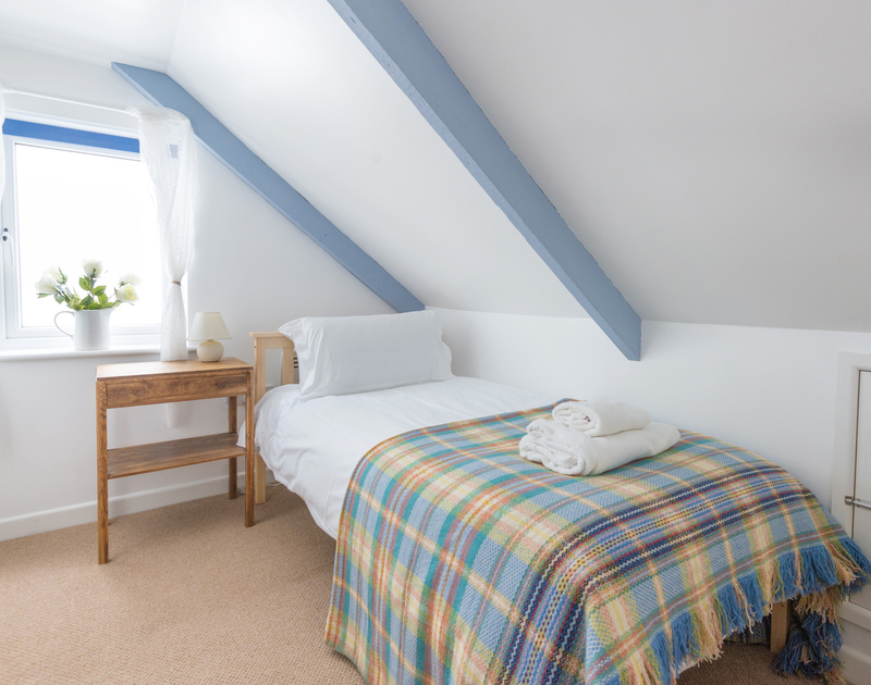 Pretty blue painted exposed beams and a vaulted ceiling in the single bedroom at self catering holiday cottage Tregenna in Port Isaac, North Cornwall.