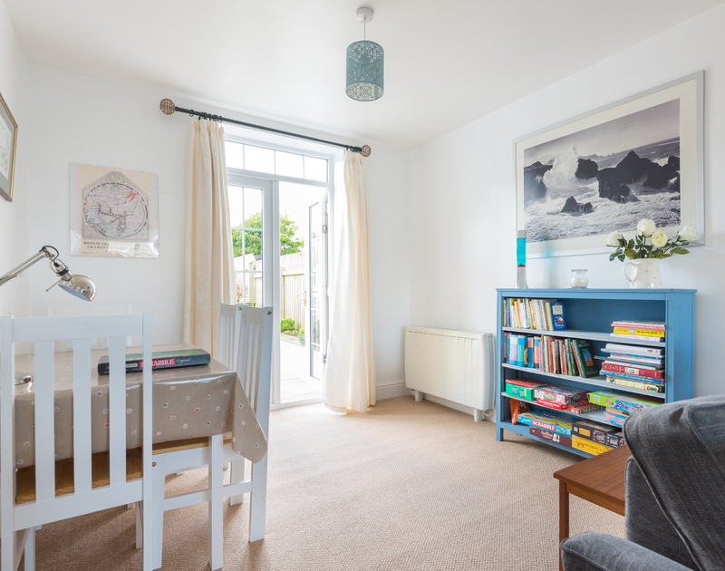 Play a family board game at the table in the sitting room beside the patio doors in Tregenna, a self catering holiday cottage in Port Isaac in North Cornwall.