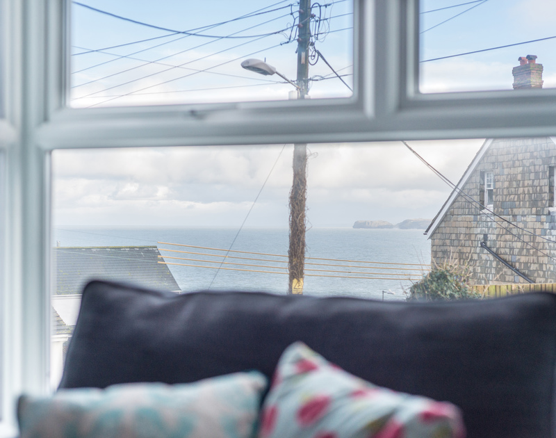 The sea and coastal views through the sitting room window at self catering holiday cottage Tregenna tucked away at the top of the village of Port Isaac on the North Cornwall Coast.