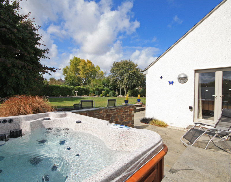 Lounge around in the jacuzzi in the sheltered and peaceful garden at holiday rental Penolver in Rock.