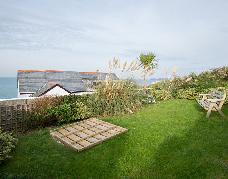 The lawned, west facing garden with a sand pit and gate at Cliffside 1, a self catering family holiday property in a fantastic setting on the cliff top at Port Isaac in North Cornwall.
