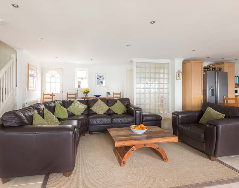 Large corner sofa in the open plan living areas in self catering holiday house Cliffside 1 set on the cliff top between Port Isaac and Port Gaverne in North Cornwall.